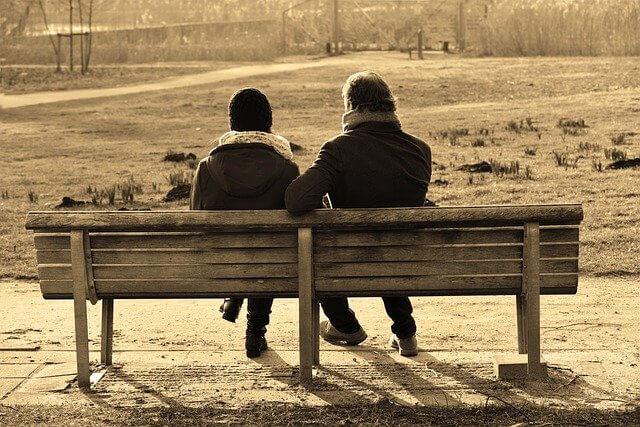 冬にベンチに座って寄り添う男女