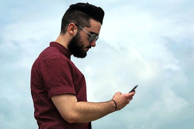 iPhoneを触る水玉の赤いシャツを着た筋肉質の男