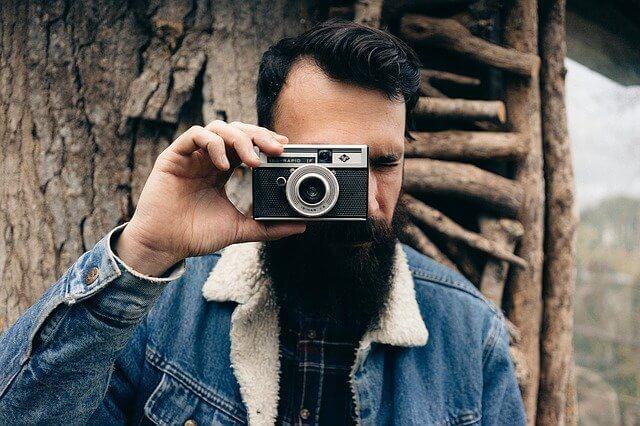 カメラを持っている黒い髭の男性