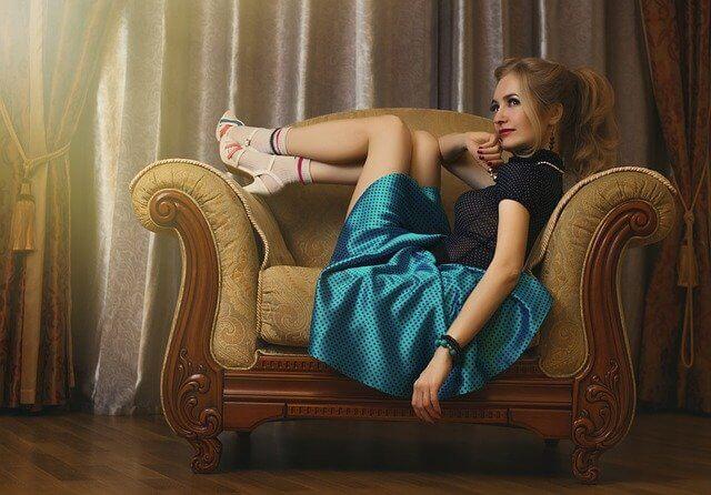 イスに座り横目で前を見るドレスを着た女性