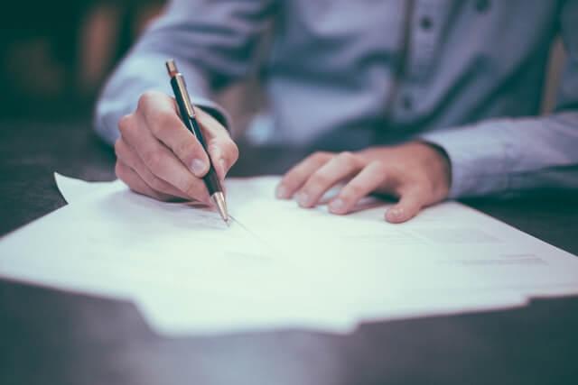 紙にペンで書く男性