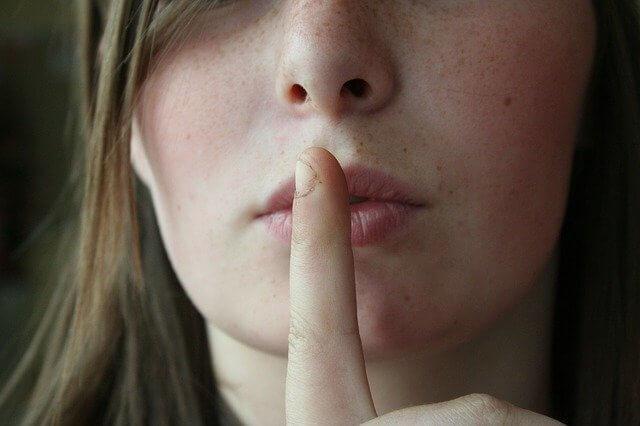 人差し指を口に当てているそばかすの女性