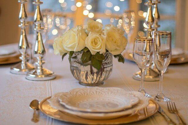 白いバラとお皿とフォークとナイフとスプーンとグラスが並べられているテーブル
