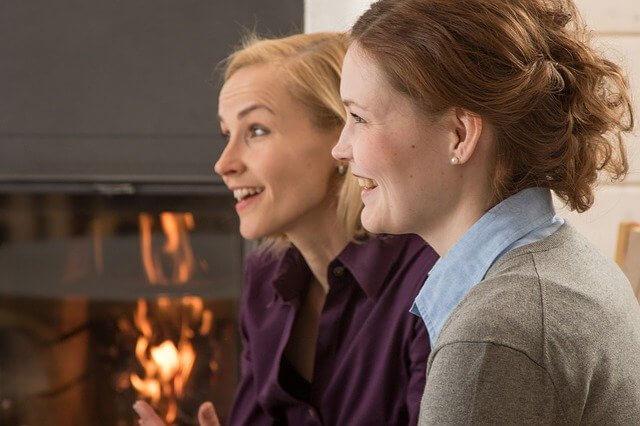 暖炉の近くで楽しく話す女性2人