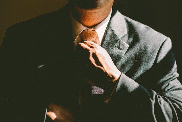 身に着けたネクタイを整えている男性