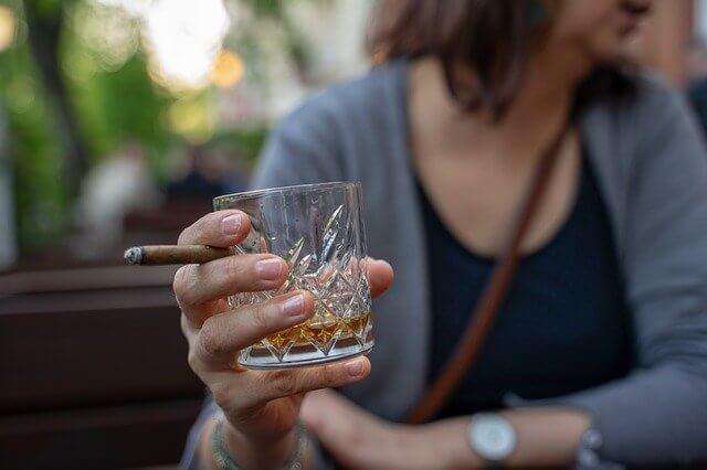 たばことウイスキーの入ったロックグラスを持つ女性