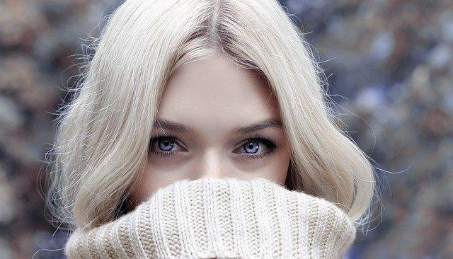 口元をセーターで隠している金髪の女性