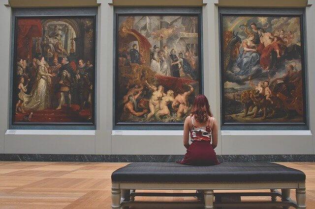 美術館のベンチに座る赤い髪の女性