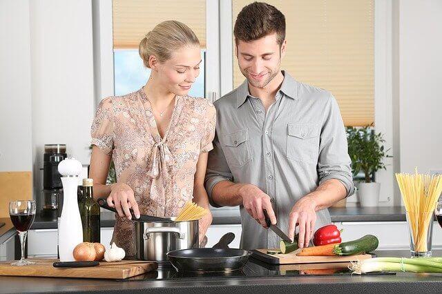 家で料理をする男女