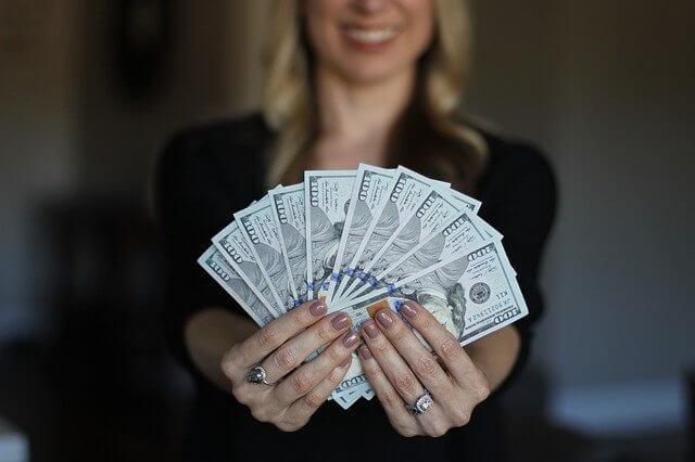 ドル札を扇状に広げる女性