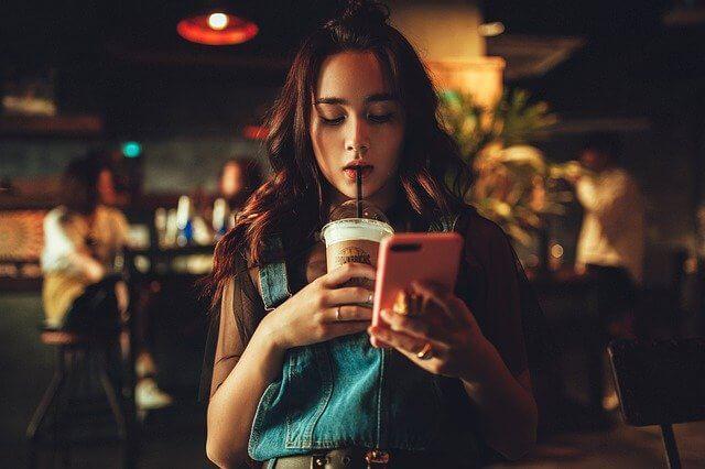 カフェでコーヒーを飲みながらスマホを触るポンパドールの女性