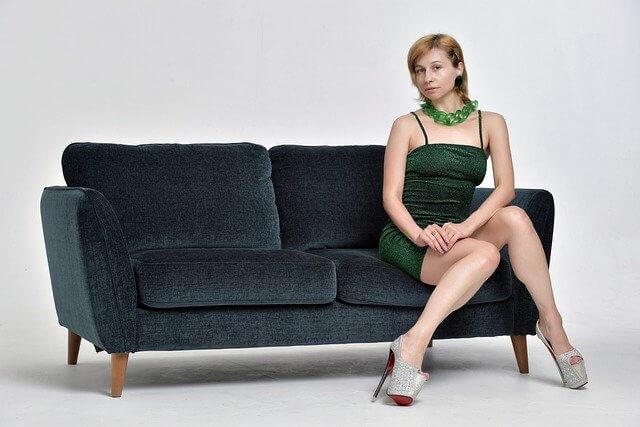 ソファに座る緑のドレスを着た女性