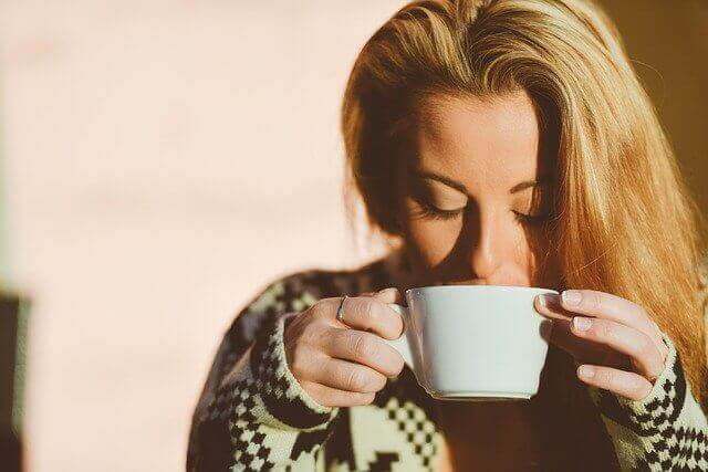 コーヒーを飲む長い髪の女性