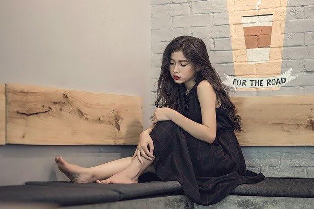 L字ソファの角で足を上げて座る黒いワンピースの女性