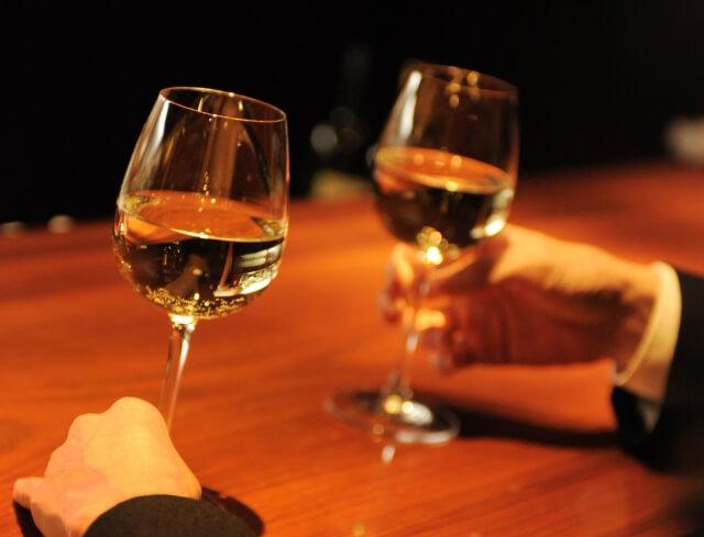 接待でワインを飲む男性